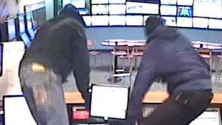 CCTV of two men jumping over the counter at Coral in Kettering.