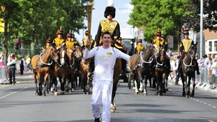 Jaco-Albert Van Gass carrying the Olympic Flame on the Torch Relay leg through Greenwich.