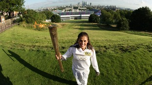 Natasha Sinha holding the Olympic Flame on the Torch Relay leg in front of the Olympic Equestrian Arena next to the Greenwich Naval Collage.