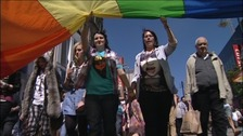 Couple holding hands under rainbow flag