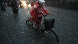 A woman cycles through the floodwater