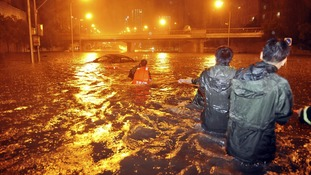Rescuers try to pull a car from a flooded Beijing street