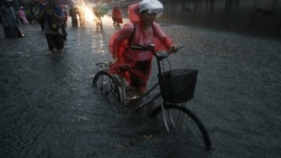 A woman cycles through the flood.