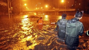 Rescuers try to pull a car from a flooded Beijing street.