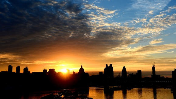 The sun rises over St Paul's Cathedral, London.