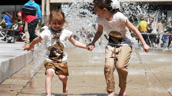 Sisters Ella (right) , aged eight, and Lilly, aged four, run through the fountains in Nottingham's Old Market Square.