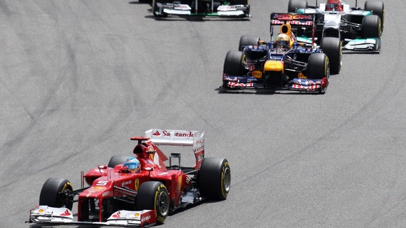 Ferrari's Fernando Alonso, left, leads Red Bull driver Sebastian Vettel, center after the start of the German F1 Grand Prix