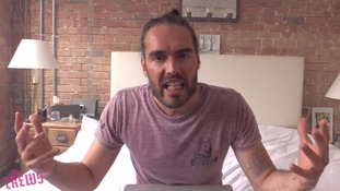 Russell Brand holds his hands up