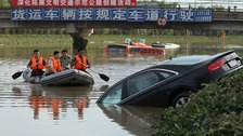 A rescue boat approaches a partially submerged car on a flooded highway after heavy rainfalls in Beijing