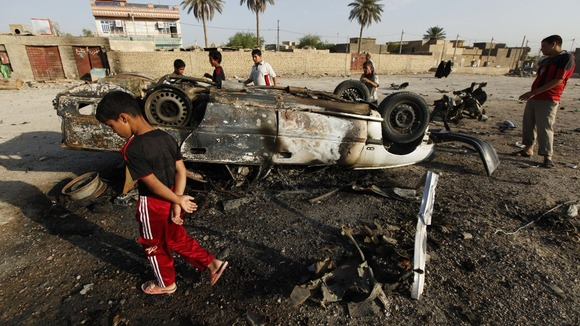 Residents gather at the site of a car bomb attack in Mahmudiya