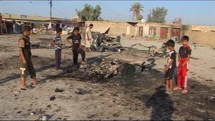 Children stand around the site of a car bomb attack in Mahmudiya, Iraq