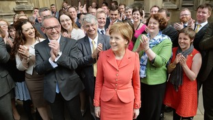 Nicola Sturgeon (front) stands with the SNP's 56 new MPs outside parliament.