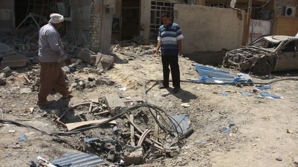 Residents inspect the site of a car bomb in the town of Taji
