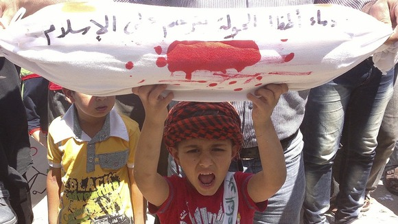 Boy holds a sack representing a dead body during a demonstration against Syria's President Bashar al-Assad in Binsh near Idlib
