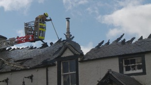 fire officer on crane above roof