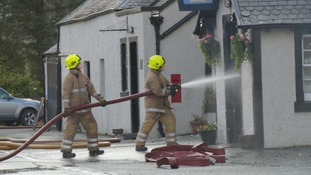 firemen use a water hose on the front door