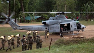 Nepalese service members load relief supplies into a U.S. Marine Corps UH-1Y Venom