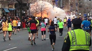 Runners continue to run towards the finish line of the Boston Marathon as an explosion erupts on April 15, 2013.