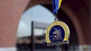 A Boston marathon medal is held outside the federal courthouse.