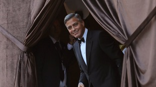 George Clooney smiles as he arrives by taxi boat to the venue of a gala dinner ahead of his official wedding ceremony in Venice September 27, 2014.