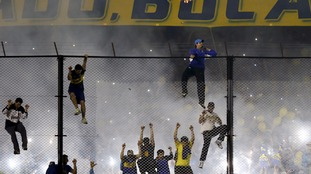 Boca Juniors fans scale the fence at the game.
