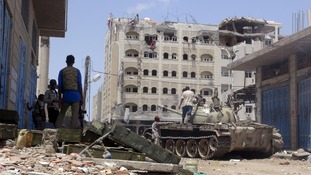 Anti-Houthi fighters of the Southern Popular Resistance stand near a tank in Yemen's southern port city of Aden