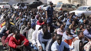 Migrants sit at a detention center after they were detained by the Libyan authorities in Tripoli.