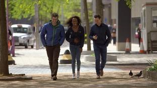 3 people walk down street