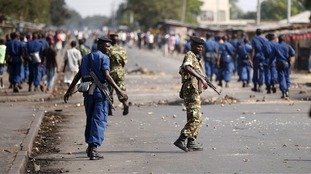 Policemen and soldiers walk on a street during a protest against Burundi President Pierre Nkurunziza.