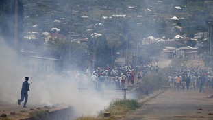 Protesters run as police fire tear gas.