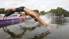A marathon swimmer dives into the Serpentine lake in Hyde Park.