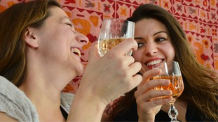 Models pose for image of two women drinking alcohol.