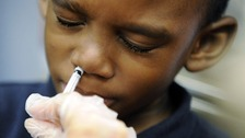 A boy is given flu vaccine in a nasal spray.
