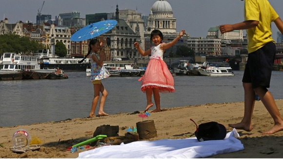 Julia Yeung and Amy Liu enjoy the hot weather on the banks of the River Thames