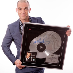 Robbie Williams with a multi-platinum award for the album I've Been Expecting You