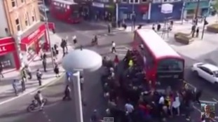 The video shows a crowd of people lifting the bus up