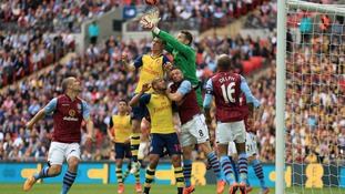 Aston Villa's goalkeeper Shay Given battles with Arsenal's Laurent Koscielny.