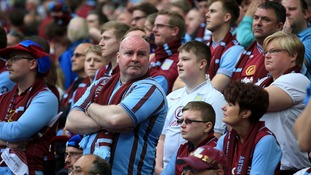 Villa fans look on nervously after seeing their side concede the first goal.