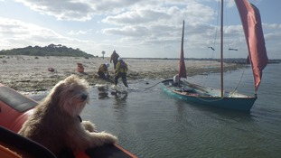 Man and his dog rescued from capsized dinghy