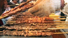 Stock photo of lamb kebabs being cooked on a griddle