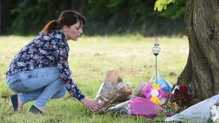 A woman lays flowers at the scene in Westfield Lane, Mansfield