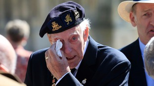 A veteran wipes his eye after attending the memorial service at Bayeux Cathedral.
