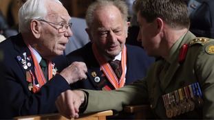 Veterans talk to an Australian army officer before the start of the memorial service.