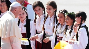 Children welcome Pope Francis as he arrives for a one-day visit at the airport in Sarajevo.