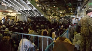Rescued migrants gathered onboard HMS Bulwark.