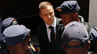 Oscar Pistorius goes to a police van after his sentencing.