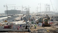 Builders and construction vehicles at work on a construction site in Doha.