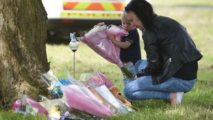 Irana Jackson and her son Finley lay flowers at the scene in Westfield Lane, Mansfield, where a body was found last night during the search for missing 13-year-old girl Amber Peat.