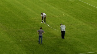 Officials inspect a swastika on the pitch