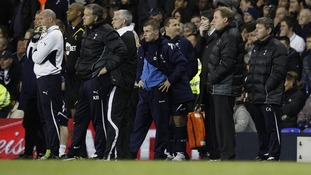 Tottenham Hotspur coaching staff look on as medical staff attend to Fabrice Muamba on the pitch